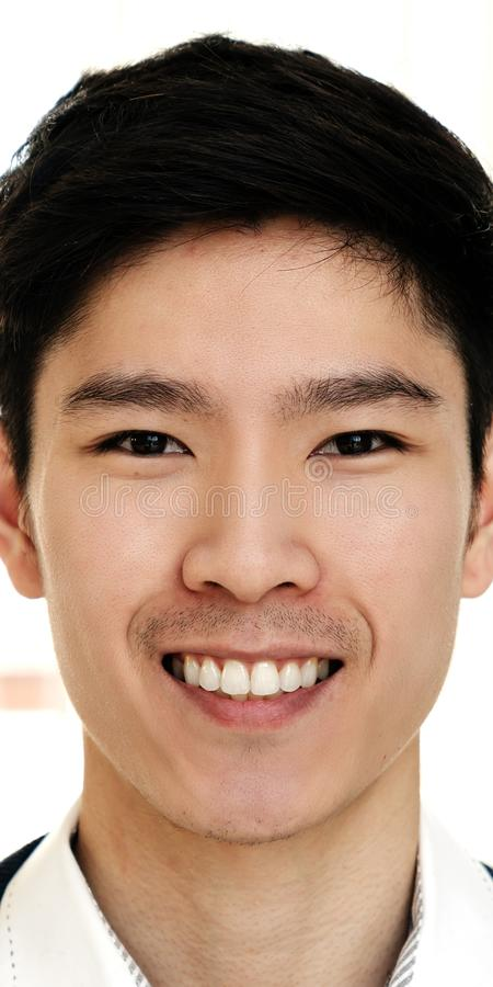 Portrait of young attractive asian creative man smiling and looking at camera in modern office royalty free stock photo