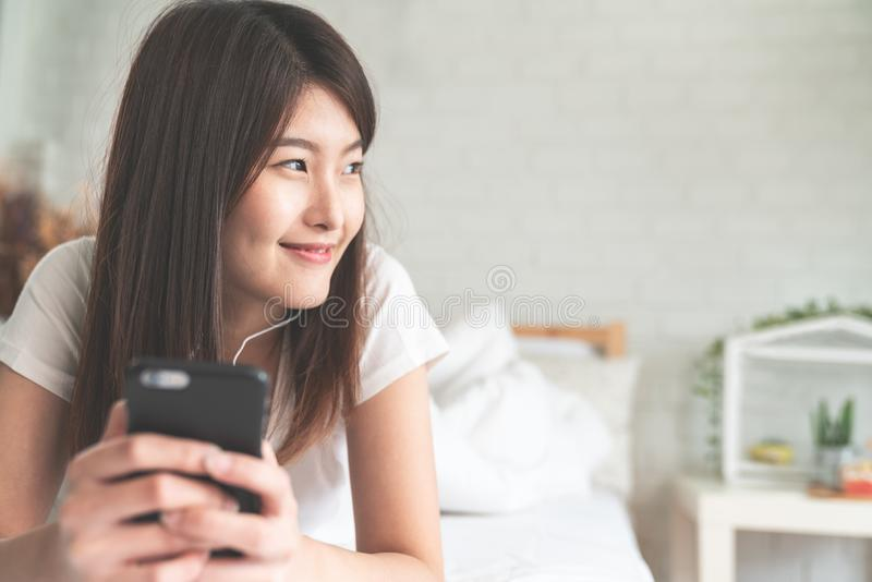 Portrait of young attractive asian woman listening to music in smartphone smiling relax on white bed and cozy bedroom with soft to stock photo