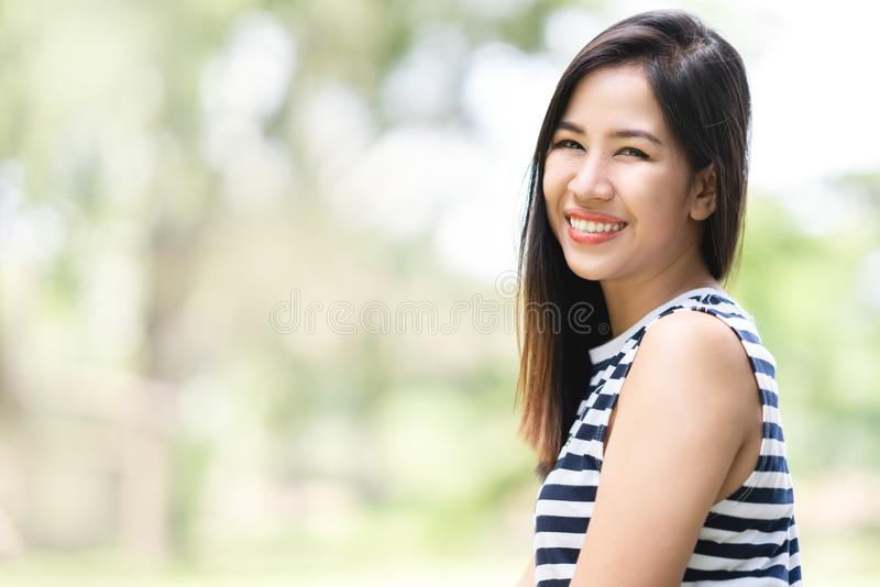 Portrait of young attractive asian woman looking at camera smiling with confident and positive lifestyle concept at outdoor park. royalty free stock image