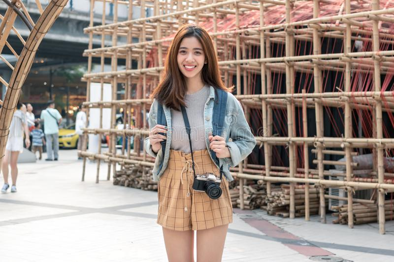 Portrait of young attractive Asian woman tourist standing outdoors in urban stock photos