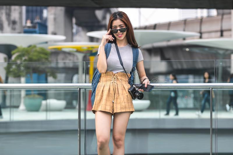 Portrait of young attractive Asian woman tourist standing outdoors in urban royalty free stock photo
