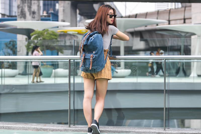Portrait of young attractive Asian woman tourist standing outdoors in urban stock photo