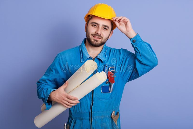 Portrait of young attractive bearded architect, builder or engineer wearing yellow helmet and blue uniform, foreman standing with stock image