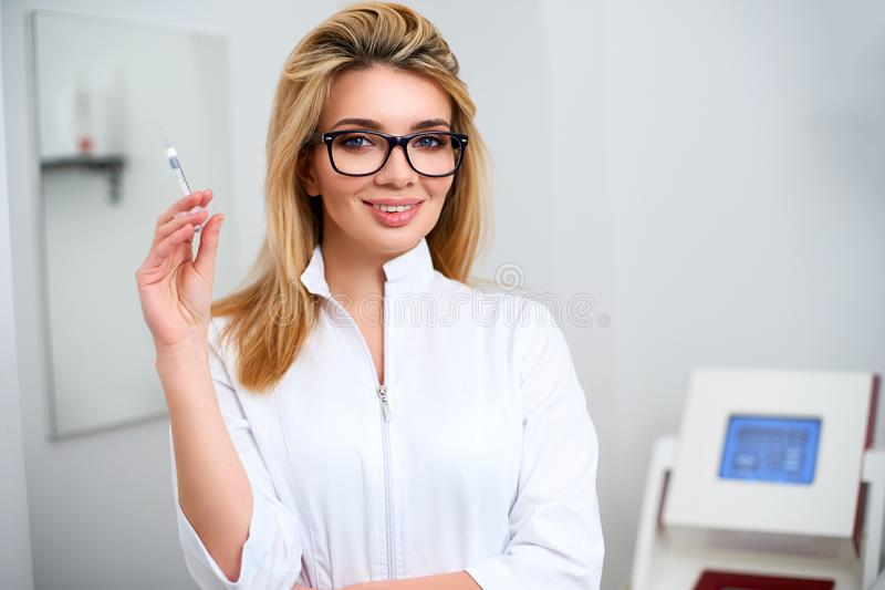 Portrait of young attractive beautician doctor with syringe in hand. Cosmetologist holding medical tools. Practician in royalty free stock photography