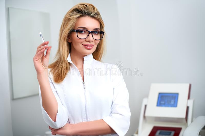 Portrait of young attractive beautician doctor with syringe in hand. Cosmetologist holding medical tools. Practician in stock image