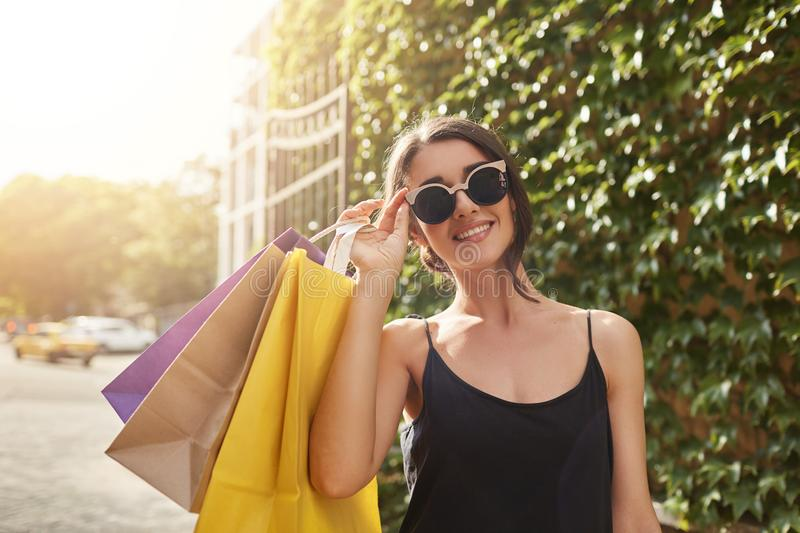 Portrait of young attractive brown-haired european woman in sun glasses and black clothes smiling in camera, holding big. Amount of shopping bags after buying stock photography