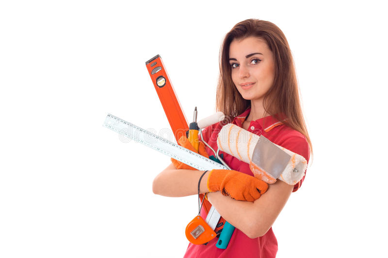 Portrait of young attractive brunette building woman in red uniform with tools in hands makes renovation and looking at stock images