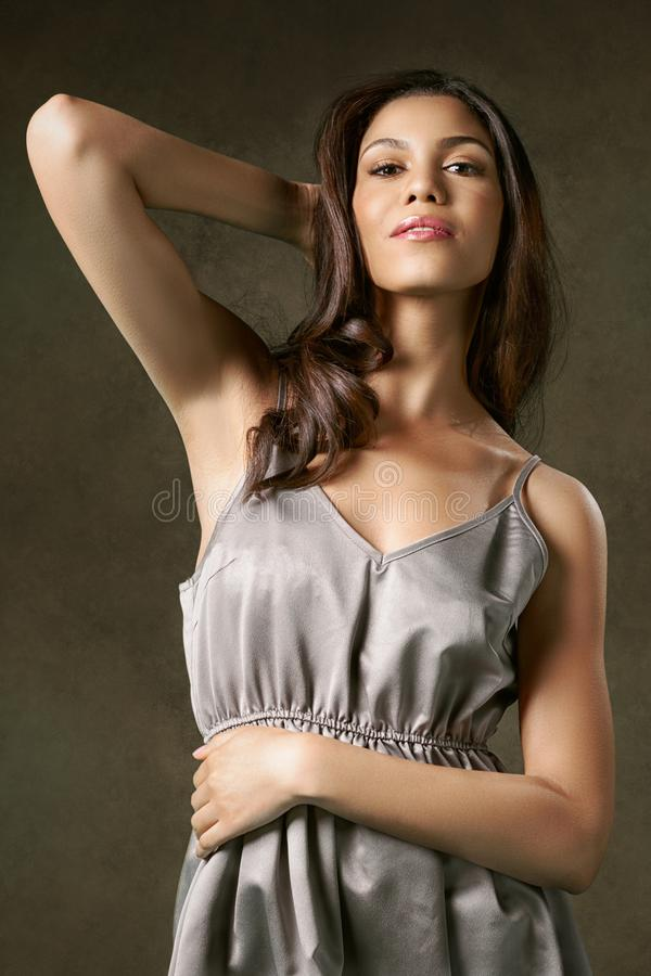 Young, attractive woman in a silver night dress. royalty free stock image