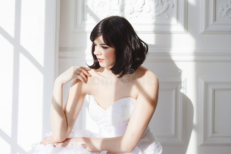 Portrait of young attractive brunette with short hair in a wedding dress. Standing at the white walls. Joyful bride. stock photography