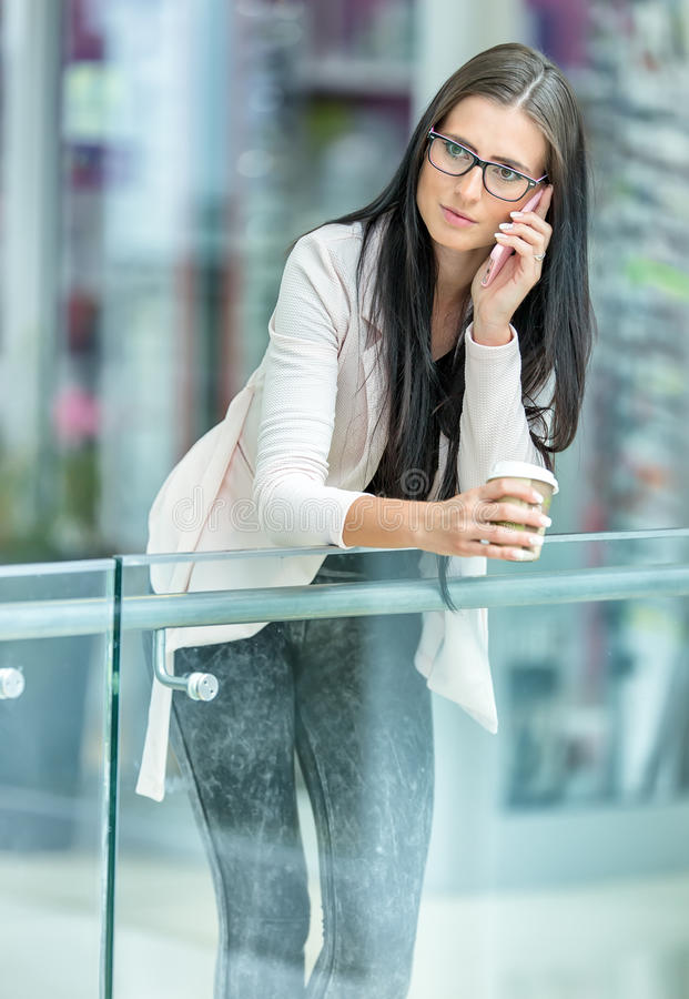 Portrait of young attractive business woman standing in the shopping mall with coffee and using her cell phone. Business break. royalty free stock photography