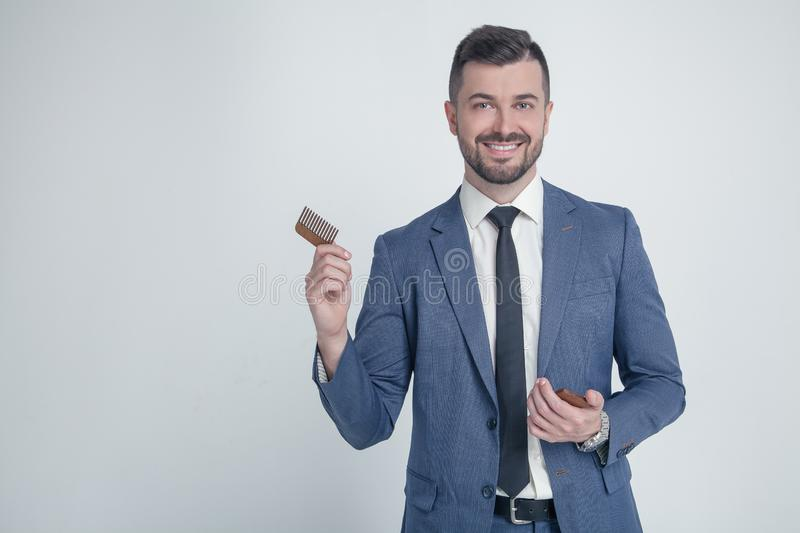 Portrait of young attractive businessman with smiling look, holding wooden comb. Stylish bearded barber in suit combing in salon. stock image