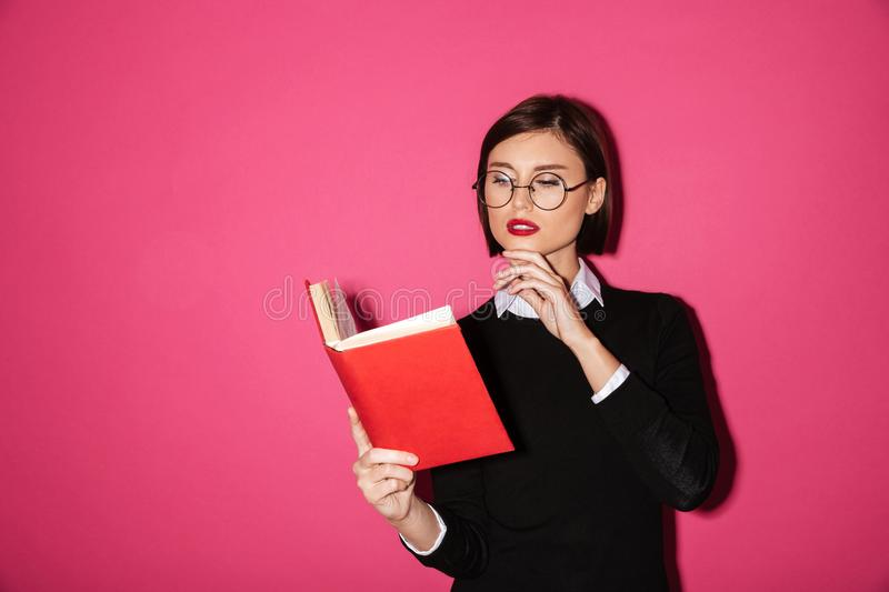 Portrait of a young attractive businesswoman reading. A book over pink background stock image