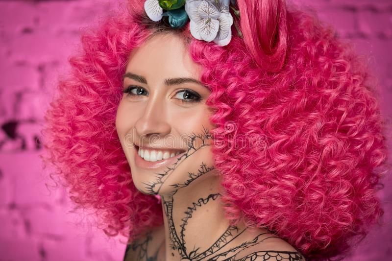 Portrait of young attractive caucasian girl model with afro style curly bright pink hair, tattooed face and flowers woven into her royalty free stock images