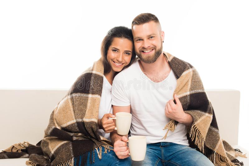 portrait of young attractive couple having coffee sitting on couch with checkered plaid, stock photo