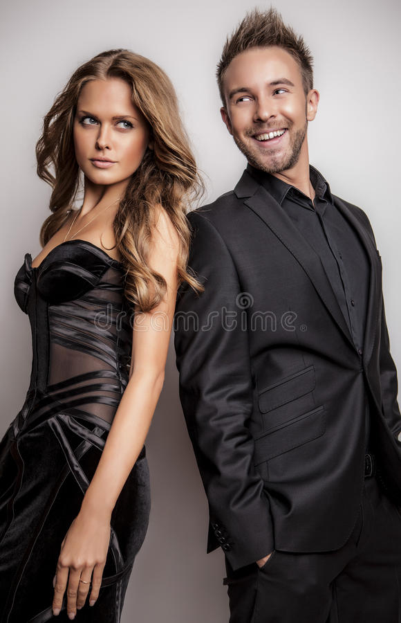 Portrait Of Young Attractive Couple Posing At Studio Dressed In Black Fashionable Clothes. Stock Photography
