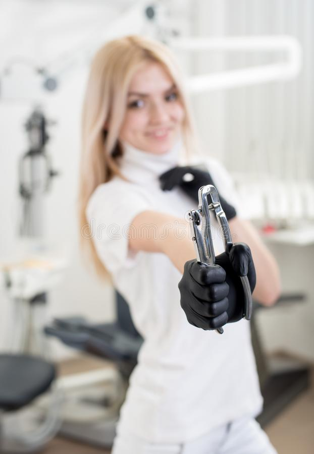 Portrait of young attractive female dentist holding dental tool at the modern dental office. Smiling female dentist with black gloves holding dental equipment at stock images