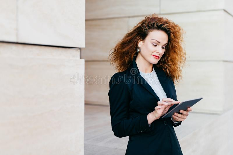 Portrait of young attractive female entrepreneur working on new business project using electronic gadget, having pleased look into royalty free stock photos