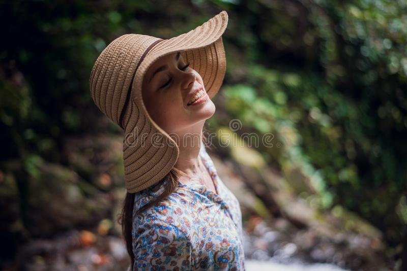 Portrait of young attractive female smiling in a jungle forest, summer vacation. Young woman enjoying fresh air in the stock image