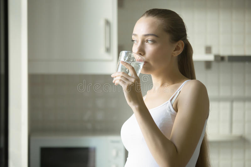 Portrait of a young attractive girl drinking water. In the kitchen. Health care concept photo, lifestyle stock photos