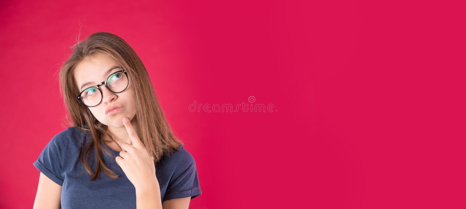 Portrait of young attractive girl with glasses holding her chin looking sideways on red pink background stock photo
