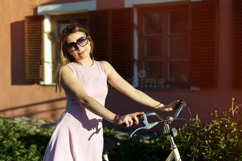 Portrait of a young, attractive girl in glasses and a pink dress on a bicycle royalty free stock image
