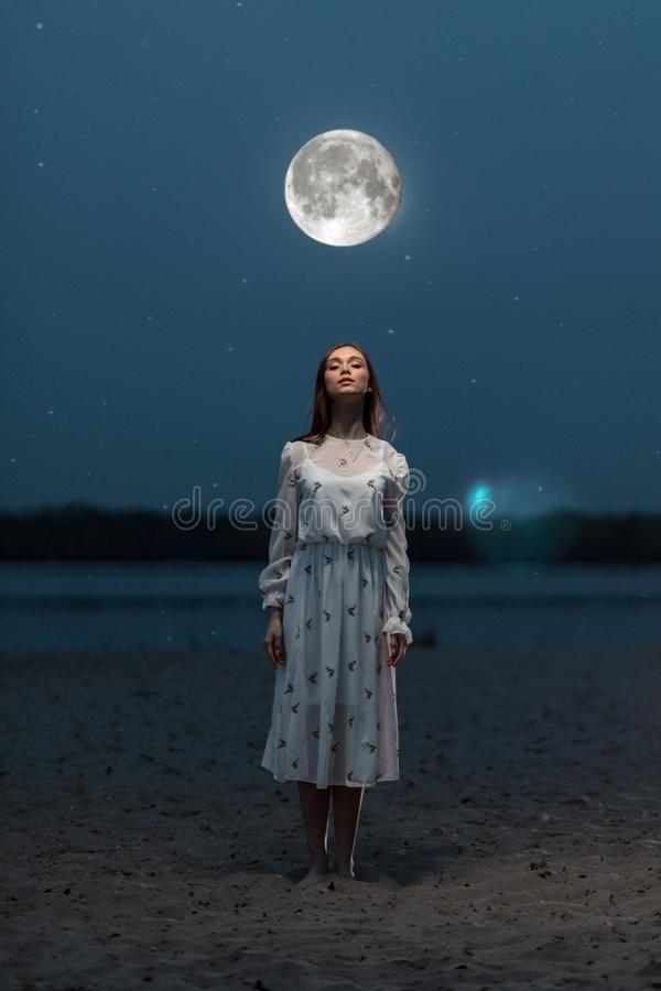 Portrait of a young attractive girl in the light of the moon. stock photo