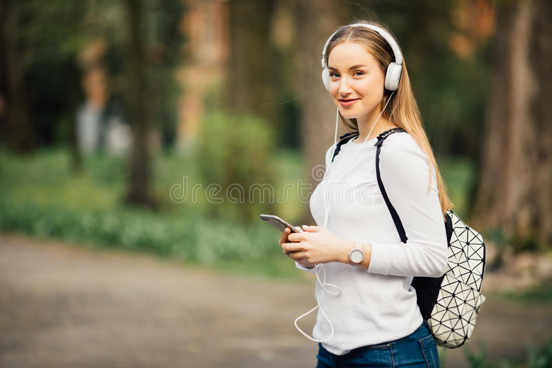 Portrait of young attractive girl in urban background listening to music with headphones stock images
