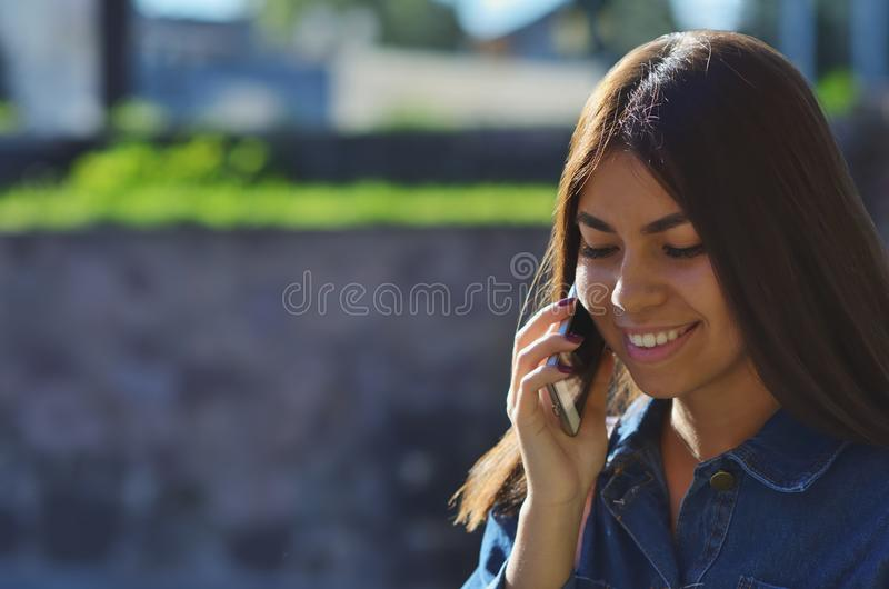 Portrait of a young attractive girl who talks on the phone on the street. And smiles, background, woman, business, fashion, person, summer, nature, internet stock image