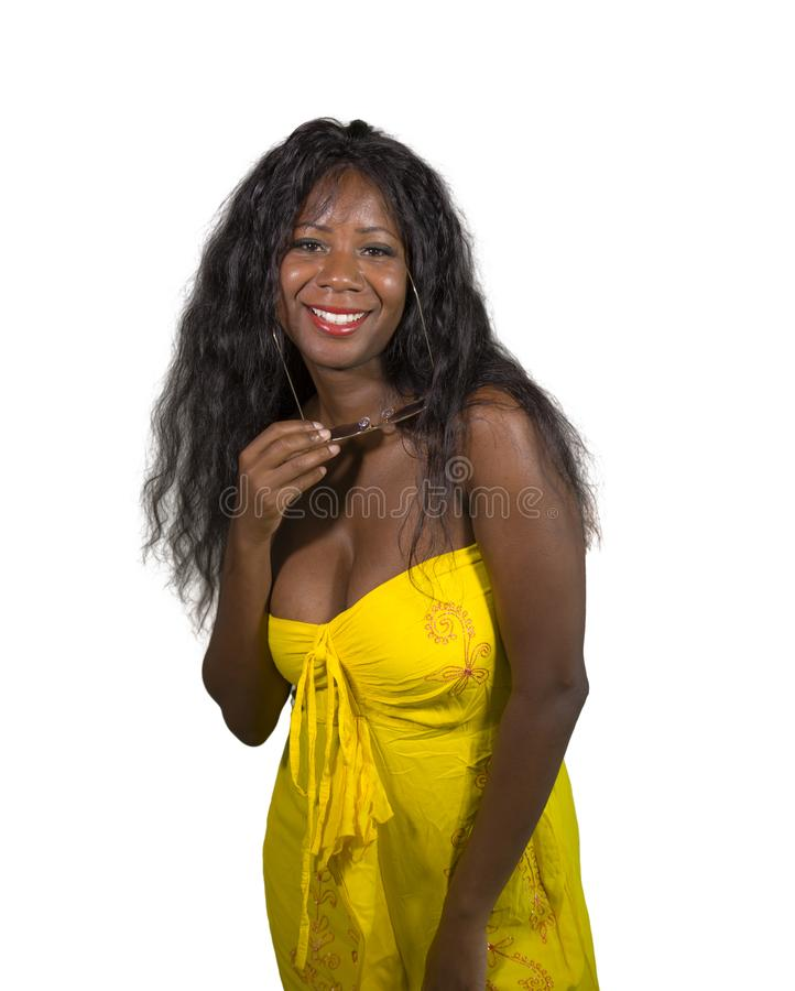 Portrait of young attractive and happy black African American woman in elegant yellow dress posing cool smiling cheerful and stock photo