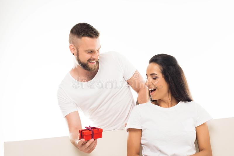 portrait of young attractive man surprising his girlfriend by gift, royalty free stock photography