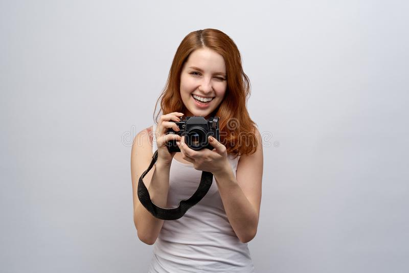 Portrait of young attractive redhead girl photographer in a white t-shirt with camera in hand. royalty free stock photography