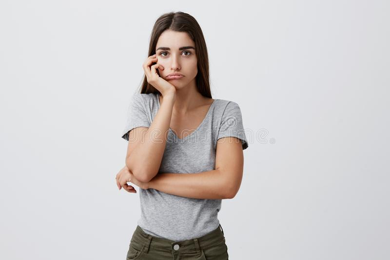 Portrait of young attractive sad charming caucasian female student with dark long hair in stylish gray outfit holding stock photos
