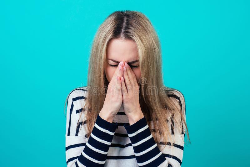 Portrait of a young attractive sick female person with blonde hair and makeup cough and sneeze in the studio on a blue stock photography