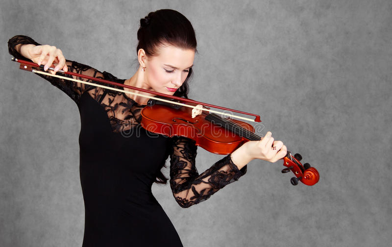 Portrait of a young attractive violinist woman in a black evening dress. Over grey background stock photography