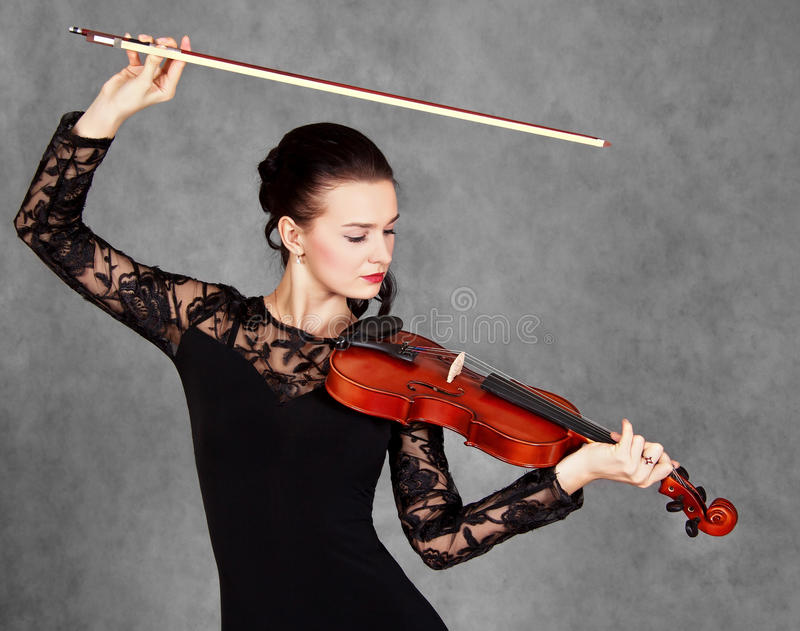 Portrait of a young attractive violinist woman in a black evening dress. Over grey background stock photo