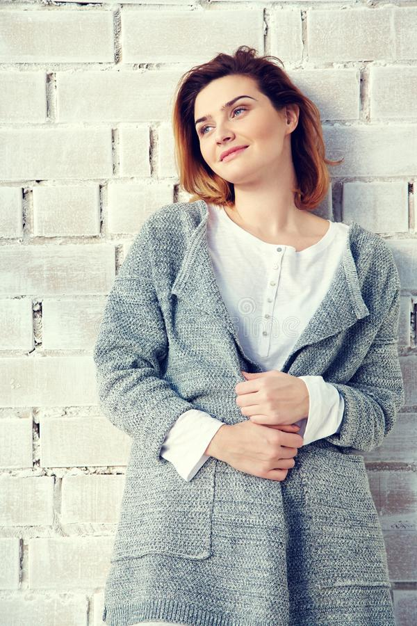 Portrait of a young attractive woman. beautiful girl near brick wall royalty free stock photo