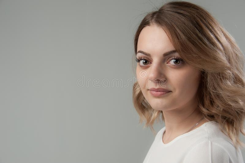 Portrait of a young attractive woman with blond hair on a neutral gray background. stock photography