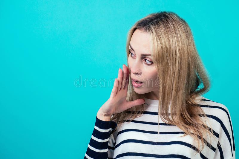 Portrait of a young attractive woman with blonde hair and makeup whispers a secret mystery in the studio on a blue royalty free stock photos