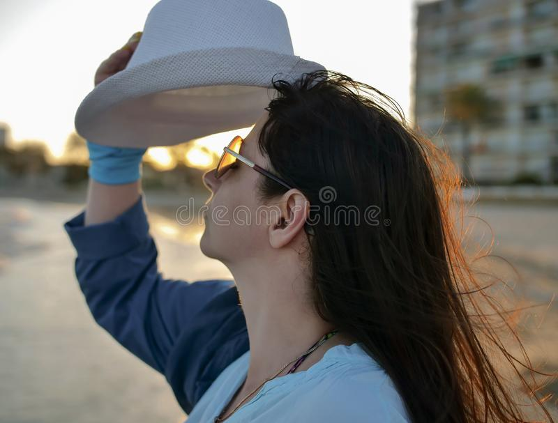 Portrait of a young attractive woman dresses a white hat, sunset royalty free stock image