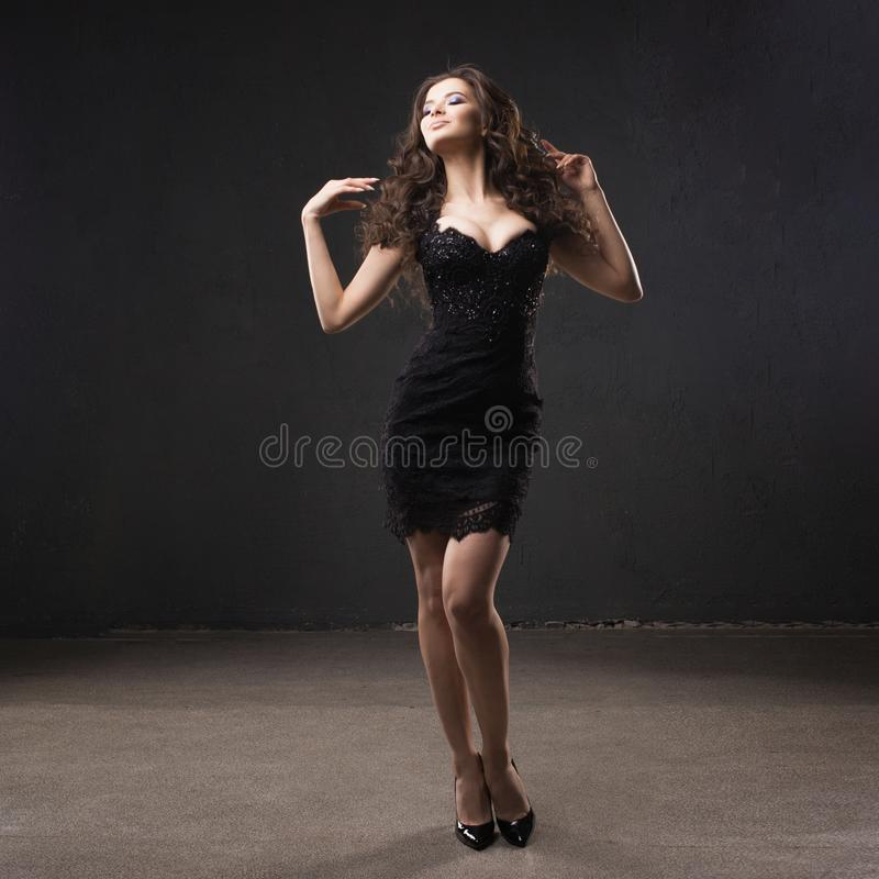 Portrait of a young attractive woman with gorgeous curly hair. young brunette in small black dress stock photography