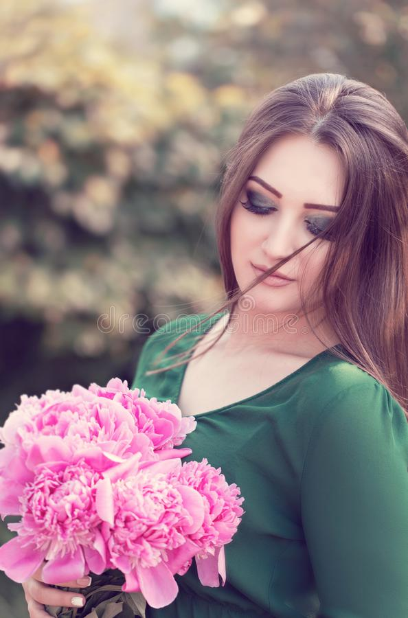 Portrait of an young attractive woman with long brown hair. With bouquet of peony flowers enjoying her time in the park stock image