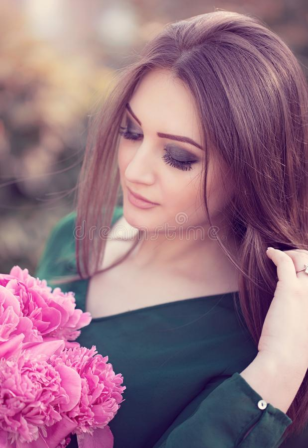 Portrait of an young attractive woman with long brown hair. With bouquet of peony flowers enjoying her time in the park stock photo