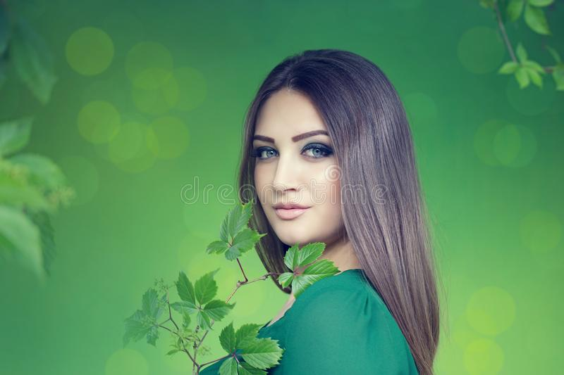 Portrait of an young attractive woman with long brown hair. Enjoying her time in the park with green wall in background stock images