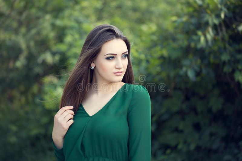 Portrait of an young attractive woman with long brown hair. Enjoying her time in the park with green tree in background stock images