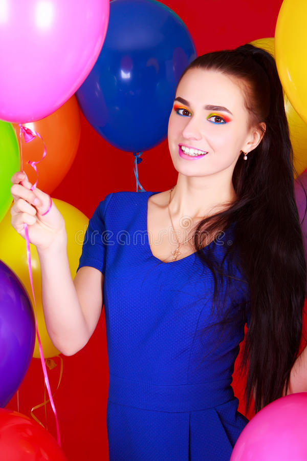 Portrait of a young attractive woman among many bright balloons. Over red background royalty free stock image
