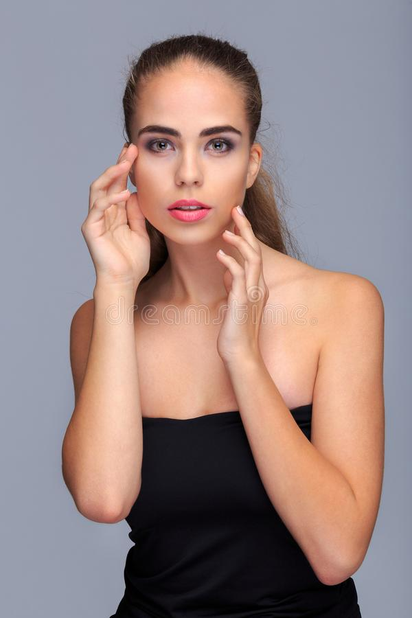 Portrait of a young, attractive woman, model, on a light gray background, cosmetics stock images