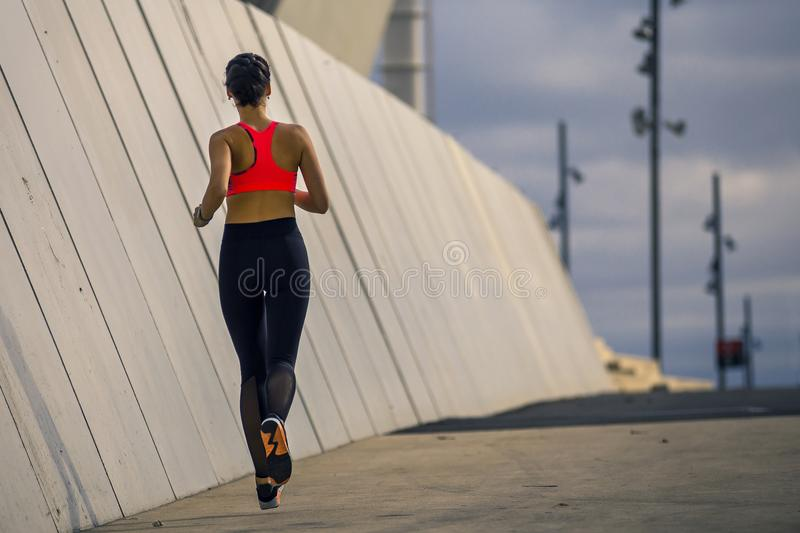 Portrait of young and attractive woman running along the wall in urban park. stock photos