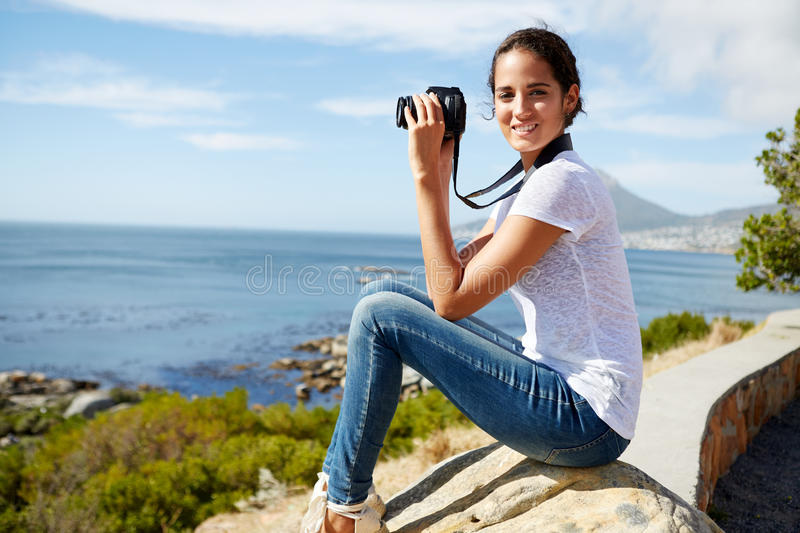 Portrait of a young, attractive woman sitting on a rock with dig stock images