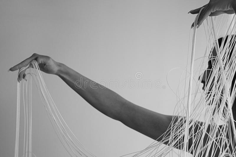 Portrait of a young attractive woman with uncovered shoulders decoratively pulling the threads of a string curtain with hands royalty free stock photography
