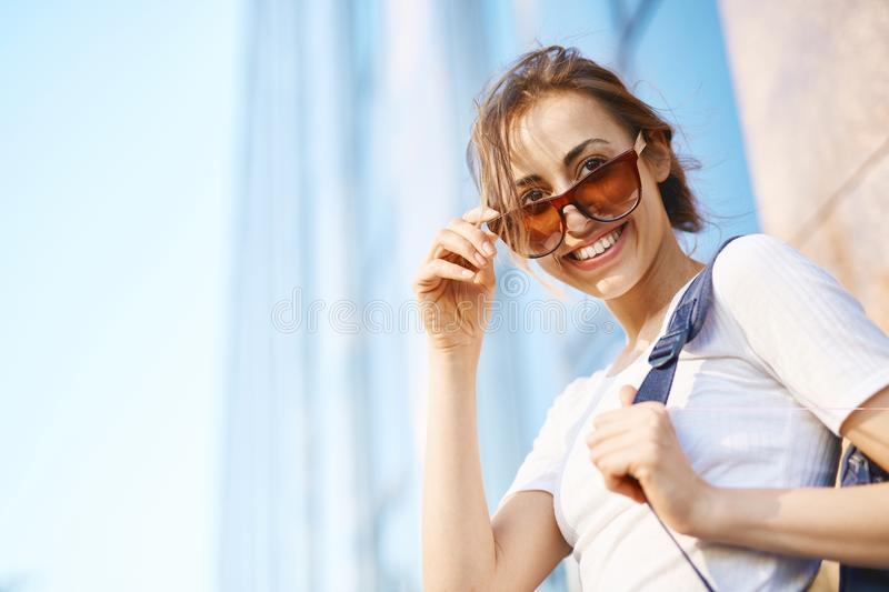 Portrait of a young attractive woman walking city at sunny day stock photo
